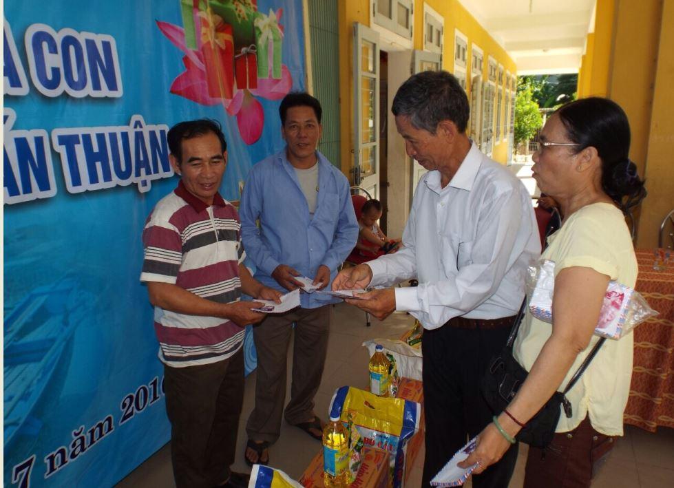 Các thành viên hội trao phong bì tiền mặt cho ngư dân